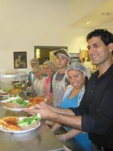 Kadwani serving pizza at pizza party
