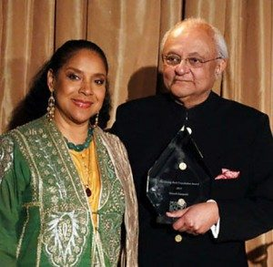 Ajit Hutheesing (left) accepts the Giving Back Award for Nimesh Kampani from emcee Phylicia Rashad
