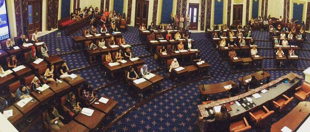 Sitting inside a scale replica of the U.S. Senate Chamber hearing from Councilor Ayanna Pressley, Samantha Washburn-Baronie, Leisha Beardmore, and Maureen Gallagher.