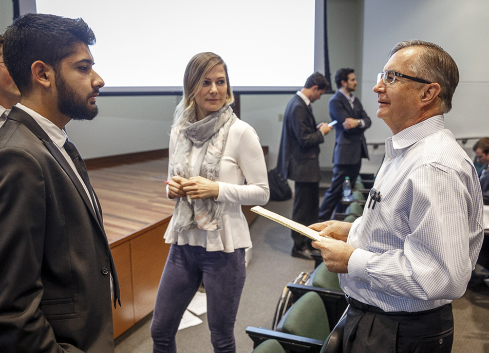 Samir Rahi, a freshman whose team placed first in the competition, and Olia Bosovik, assistant director of the IIE's Venture Development Center, talk with Madison Pedigo, IIE academic director (Image Courtesy: utdallas.edu)