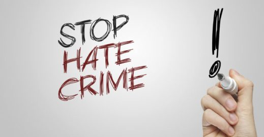 Hand writing stop hate crime on grey background