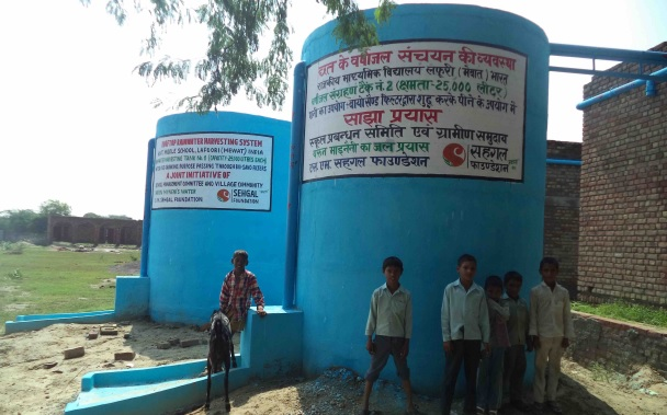 Children standing before a water tank in the village of Lafuri in Haryana.