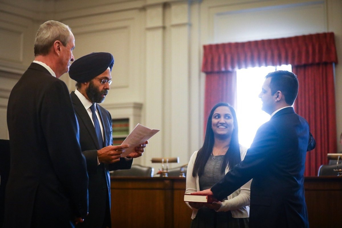 Attorney General Gurbir Grewal administering the oath to lawyer Parthiv Patel, as Governor Phil Murphy (left) looks on.