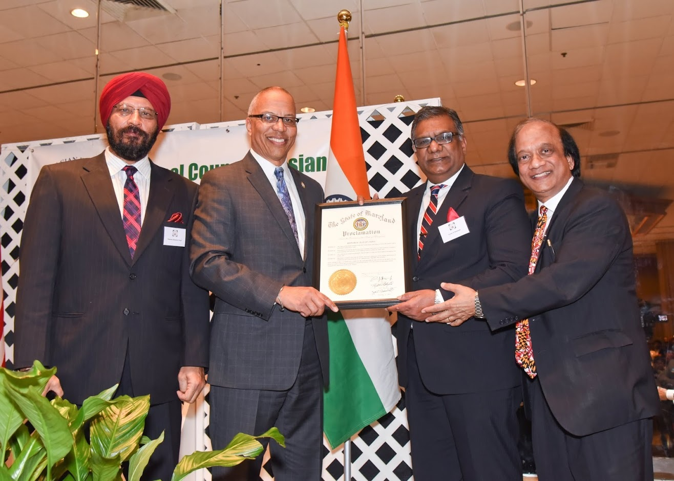 Maryland Lt. Governor Boyd Rutherford (second left) handing over a proclamation from the Governor of Maryland to NCAIA President Pavan Bezwada (second right) and Chairman Dr. Suresh K. Gupta (right).