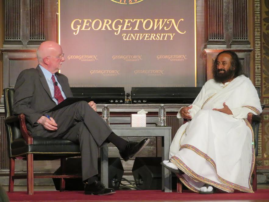 """Spiritual leader Sri Sri Ravi Shankar (right) in conversation with Shaun Casey, director of Georgetown University's Berkley Center for Religion, Peace and World Affairs. The event, titled """"Interfaith Harmony and Service,"""" was hosted by the university's India Initiative on April 22, 2018, at Georgetown's Gaston Hall."""