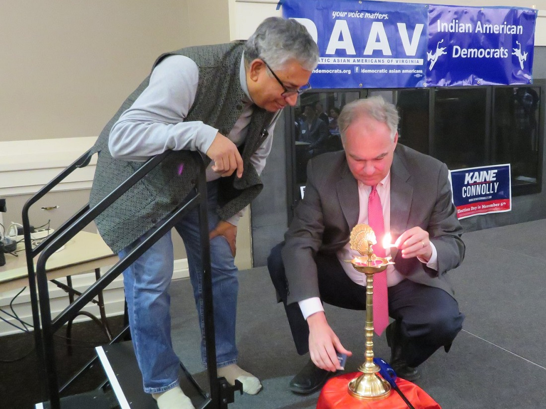 "Sen. Tim Kaine lighting the ""diya"" (lamp) at a Diwali celebration co-hosted by Democratic Asian Americans of Virginia (DAAV) and Virginia's 11th Congressional District Democratic Committee (CDDC). Looking on at left is Shekar Narasimhan, chairman of AAPI Victory Fund."