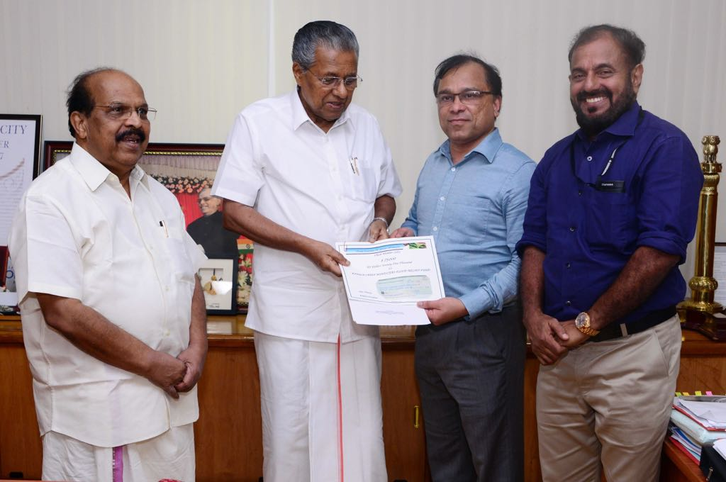 Kerala Chief Minister Pinarayi Vijayan (second from left) receiving a check for $75,000 from KAGW Saju Thomas (second from right) toward the state's flood relief fund. On the left is Minister for Public Works Department and Registration G. Sudhakaran.