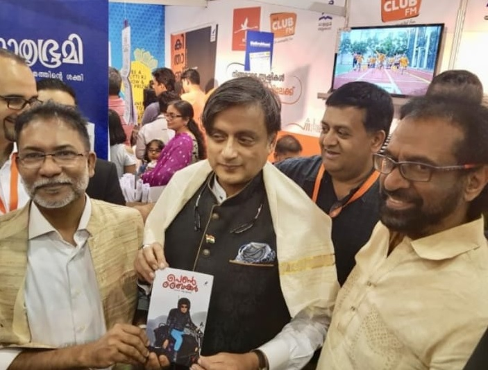 "Shashi Tharoor (center) giving a copy of ""The Lady Biker"" to Shajahan Madampat a the Sharjah International Book Fair on November 9. Looking on is author Thampi Antony."