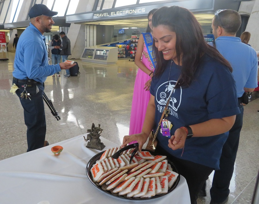 Akanksha Sharma, marketing associate for Metropolitan Washington Airports Authority, hands out cookies embellished with 'Happy Diwali' at Dulles Airport