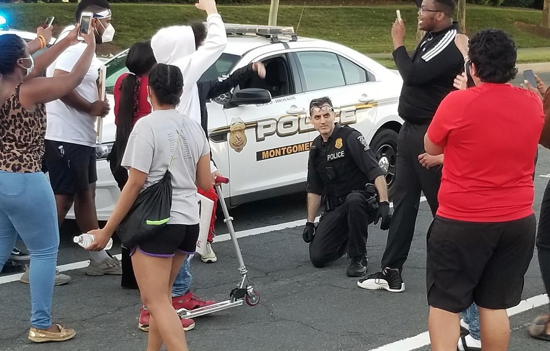 A policeman from the Montgomery County Police Department takes a knee in solidarity during peaceful protest in Germantown, MD, Sunday evening. Photo courtesy: Montgomery Community Media